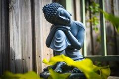 Stone statue of Buddha sitting and praying royalty free stock photography