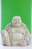 A buddha figurine against a green background Stock Photography