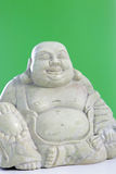 A buddha figurine against a green background Stock Photos