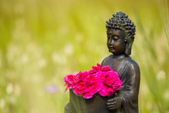 Buddha figurine with red flowers Stock Photography