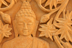 Buddha with Floral carvings on sand stone Royalty Free Stock Images