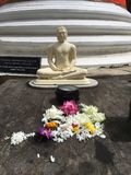 Buddha Flower Offering Table. A picture of a buddha on a offering table surrounded by flowers Stock Photo
