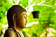 Stone statue of Buddha sitting praying and meditating for mind body soul spirit. Buddha Gautama figure zen meditating and praying to universe and god stock photography