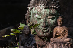 Buddha Head. Figurines and miniatures, inspired by nature, antique and vestige, green leaves Royalty Free Stock Photos