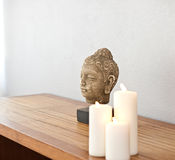 Buddha head in front of a grey wall Royalty Free Stock Photos