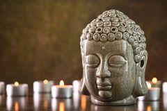 Meditation or relax spa treatment concept, front view, space for. Buddha head statue standing on a dark stone surface, burning candles all around it, meditation Royalty Free Stock Photography