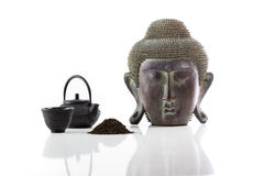 Buddha head, teapot, cup and tea on a white background Stock Photo