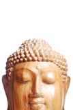 Buddha head on white. A wooden buddha head isolated in front of a white background stock photo