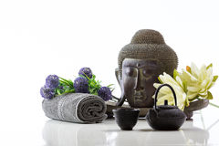 Buddha head on a white background, towel, teapot and lotus Stock Photo