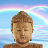 Buddha Heaven. Fantasy abstract of the face of a buddha with blue sky and double rainbow with reflection over rippled water to the rear Stock Images