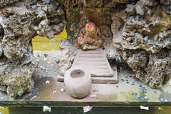 Buddha i en vagga med mynt och räkningar runt om honom Royaltyfria Bilder