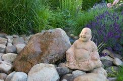 Buddha im grünen Garten mit Steinen und Wasser Stockbilder