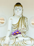 Buddha image statue with fresh flowers in hands Royalty Free Stock Photos