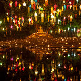 Buddha image surrounded by candles and colourful. stock image