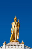 Buddha Image in walking attitude. With blue sky, Thailand royalty free stock photography