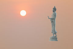 Buddha image in walking posture. On orange background with sun Royalty Free Stock Photography
