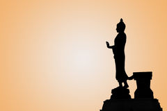 Buddha image in walking posture. On orange background with sun Royalty Free Stock Image