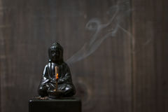 Buddha Incense Holder: Smoking. Smoking Budha incense holder against wooden background Stock Photography