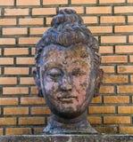 Buddha-Kopf auf Backsteinmauerhintergrund lizenzfreie stockfotos