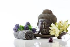 Buddha-Kopf auf einem weißen Hintergrund, einem Tuch, Steinen und einem Lotos Lizenzfreies Stockfoto