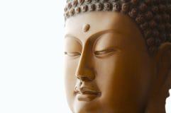 Buddha-Kopf, der gegen einen weißen Hintergrund schnitzt Stockfotografie