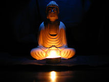 Buddha Light. A small candle in front of a carved wooden idol of buddha lit with blue light from above Stock Photos