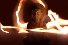 Buddha light painting. Buddha statue with dark background and a candle in front Stock Photos