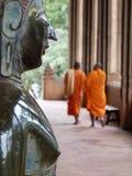 Buddha looking at 2 monks Stock Photo
