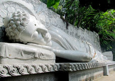 Buddha lying statue, Sleeping Buddha. Lying Buddha big marble statue. Sleeping Buddha on the sun in the buddhist temple in the jungle Royalty Free Stock Photo