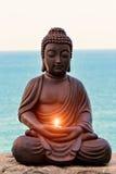 Buddha med en stearinljus i händer Arkivfoton