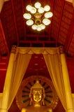 Buddha med guld- gloria under den enorma kandelaber Fotografering för Bildbyråer