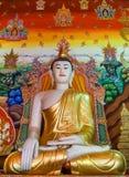 Buddha med guld- Ushnisha som är främst av den röda Thangka väggen Royaltyfri Foto