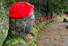 Buddha med hatten och rad av buddhas Arkivbild