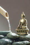 Buddha meditating next to cleaning water Stock Photography