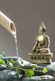 Buddha meditating next to water and foliage Stock Photos