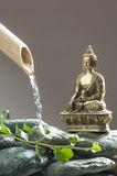 Buddha meditating next to water source Stock Images