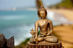 Buddha-Messingskulptur am Ozeanhintergrund Stockfotos