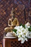 Buddha mit Duft-Steuerknüppeln und Blumen lizenzfreies stockbild