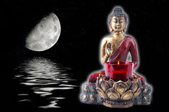 Buddha with a moon. Buddha with reflection over rippled water. Against black background with a moon on the spring equinox Royalty Free Stock Photography