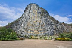 Buddha mountain. Laser carved and gold plated monumental Buddha stock photo