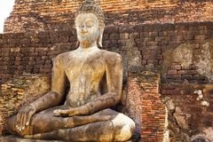 Buddha near wall Stock Images
