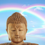 Buddha Nirvana. Smiling Buddha face with a blue sky and double rainbows with reflection over rippled water to the rear Stock Images