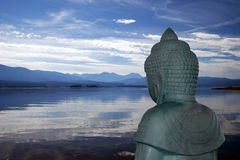 Buddha overlooking lake. Backview of Buddha statue overlooking a peaceful mountain lake stock photos