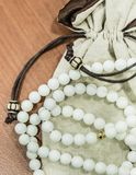 Buddha pearl necklace with bag display on table closeup view. Buddha pearl necklace with bag closeup view stock photo