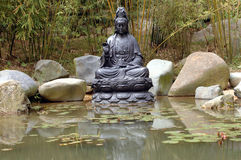 Buddha at pond. Buddha sculpture surrounded by water from small pond with lotus flowers and bamboo trees Stock Photo