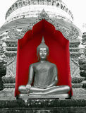 Buddha in Red. Buddha statue sitting in the lotus position in front of a Chedi at a Wat or Temple in Chiang Mai, Thailand. Taken in Black & White in a red alcove Stock Photography