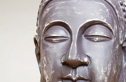 Buddha`s face close-up. The Buddha image in ceramics. The texture of the background and focus of the soft focus. For an atmosphere of meditation stock photo