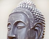 Buddha`s face close-up. The Buddha image in ceramics. The texture of the background and focus of the soft focus. For an atmosphere of meditation royalty free stock images