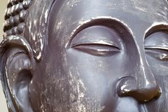 Buddha`s face close-up. The Buddha image in ceramics. The texture of the background and focus of the soft focus. For an atmosphere of meditation stock images