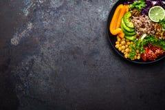 Buddha-Schüsselteller mit Naturreis, Avocado, Pfeffer, Tomate, Gurke, Rotkohl, Kichererbse, frischem Kopfsalatsalat und Walnüssen lizenzfreie stockfotos
